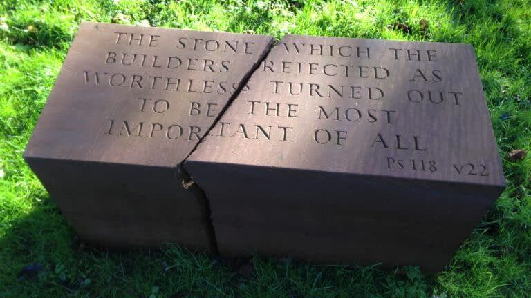 """Red sandstone foundation stone, cracked through the middle. The inscription on the top reads: """"The stone which the builders rejected as worthless turned out to be the most important of all"""". From Psalms 118, verse 22"""