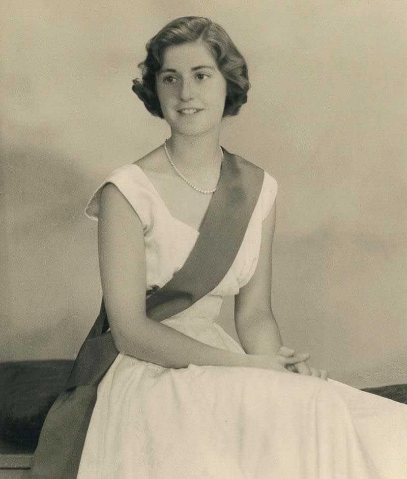 Doreen as a young woman, wearing a long white dress with a wide sash