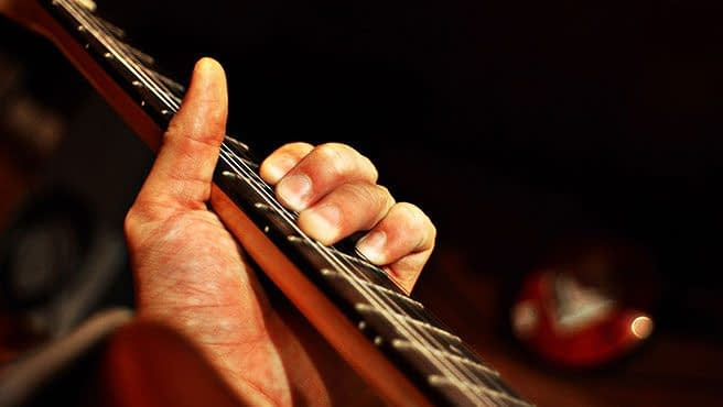 Close up of man playing an acoustic guitar