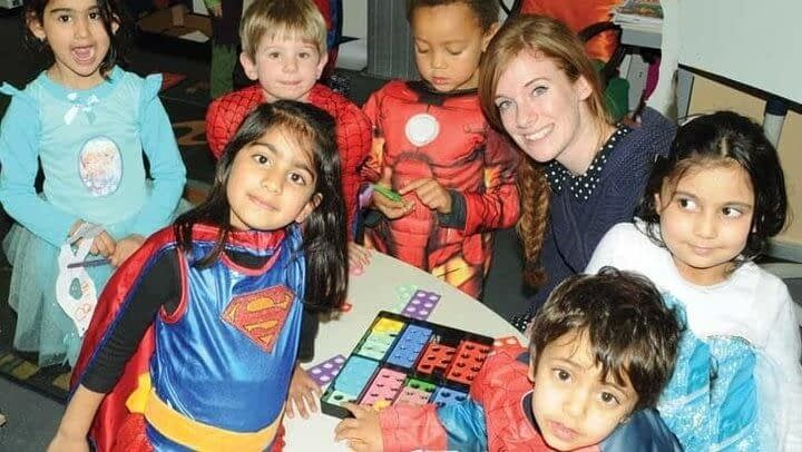 Five children in superhero costumes play with bricks around a table