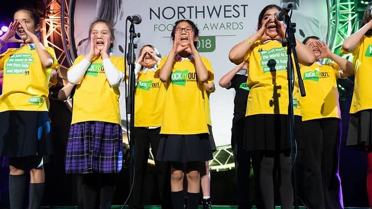 Singers cup their hands to their mouths as they sing about spreading the word