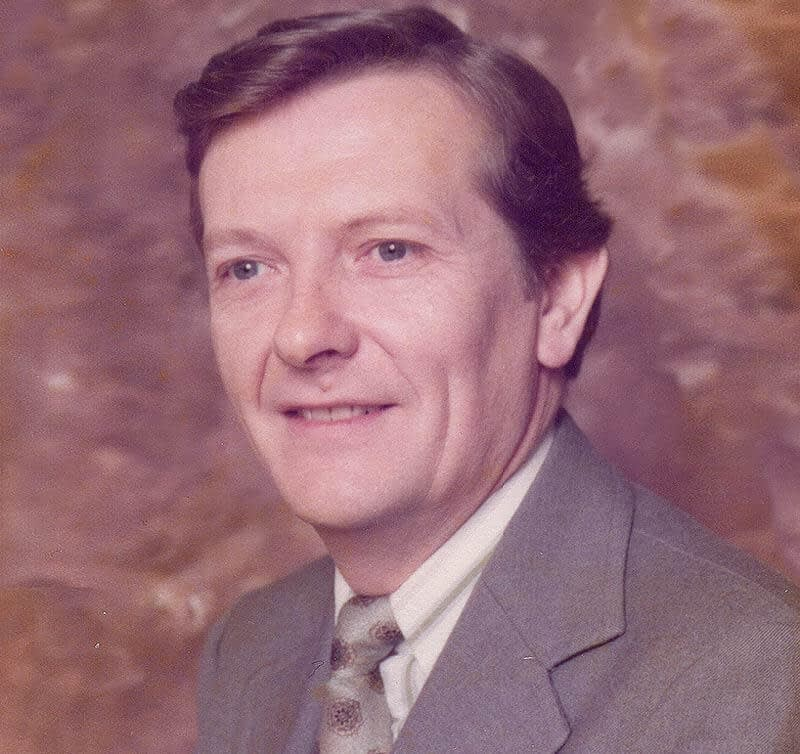 A colour portrait photograph of Alex, wearing a jacket and tie