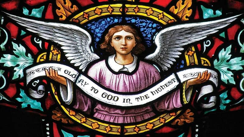 Detail of a Victorian stained glass window in Emmanuel, showing an angel holding a scroll that says: 'Glory to God in the highest'