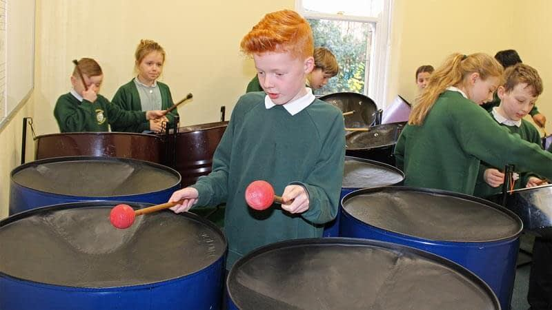 A boy enjoying playing the steel pans with his class
