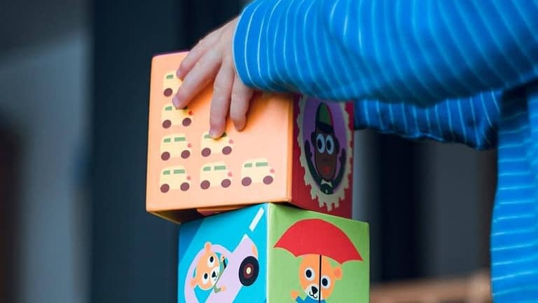 Close up of toddler's hands playing with coloured wooden bricks