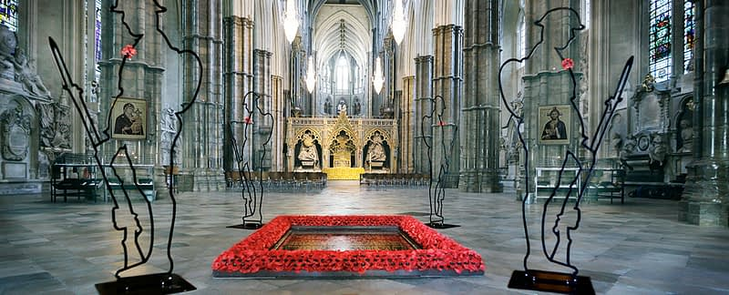 Church interior with two 'Tommy' figures guarding a square display of red poppies