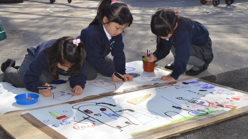 Three children kneeling in the playground as they draw pictures together on a large sheet of paper