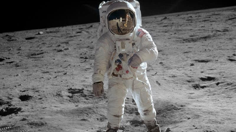 American astronaut stands on the moon's rocky surface
