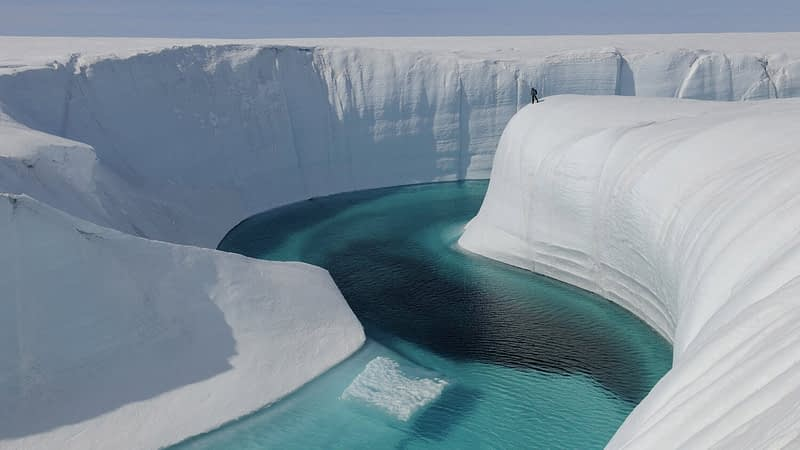 A river with clear blue water flowing through a glacier in the arctic