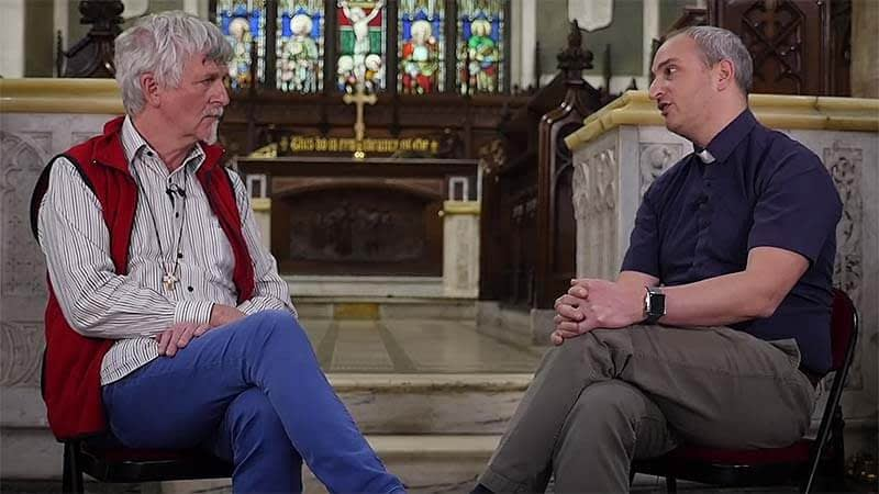 John Bell and Nick Bundock sit talking in the chancel of St James church