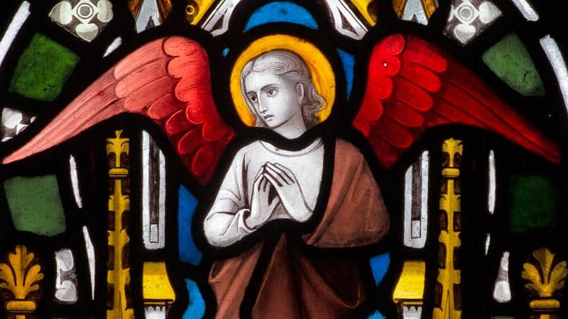 Detail of a stained glass window in Emmanuel depicting an angel with red wings