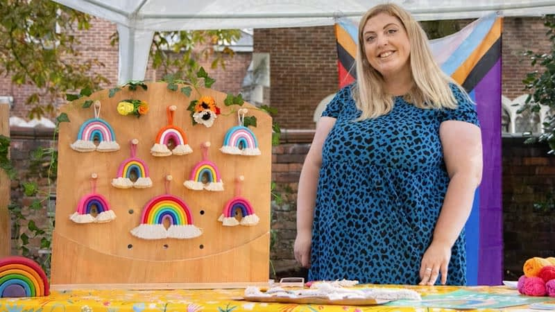 Smiling stall holder selling knitted rainbows at Didsbury Pride