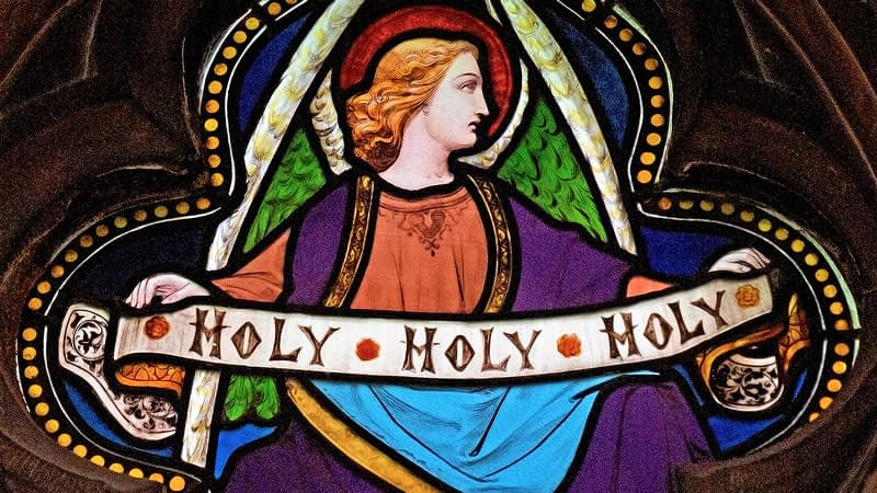 Detail of a stained glass window in Emmanuel depicting an angel holding a banner stating 'Holy, holy, holy'