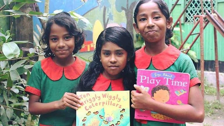 Three young smiling school girls proudly show off their reading books