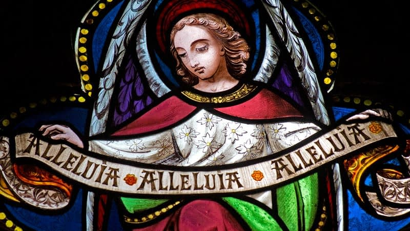 Detail of a stained glass window in Emmanuel depicting an angel holding a banner that says 'Allelulia, Allelulia, Allelulia