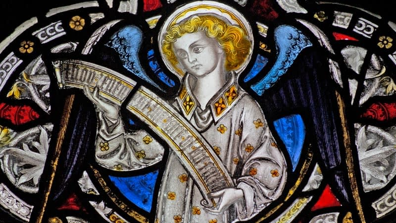 Detail of a stained glass window in Emmanuel depicting an angel with golden hair holding a scroll