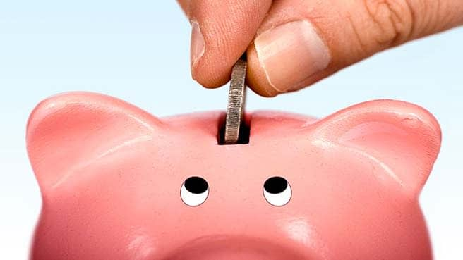 A pound coin being dropped into the slot of a pink piggy bank