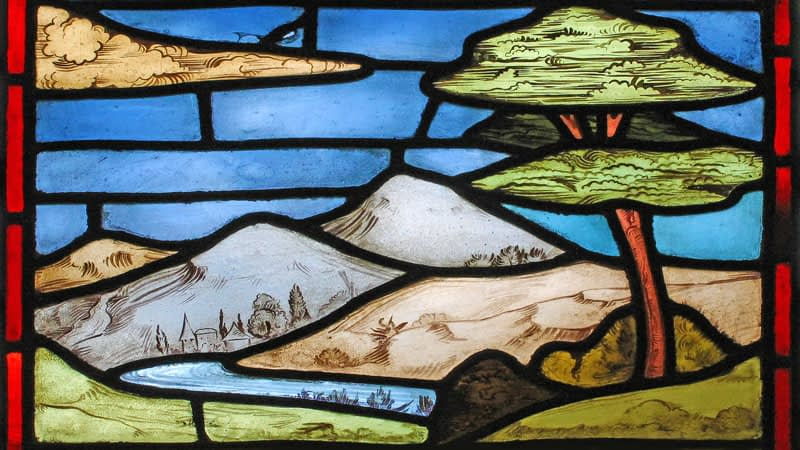 Detail of a stained glass window in Emmanuel depicting a landscape with trees, hill and a river