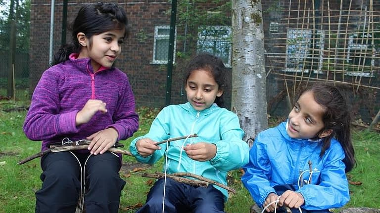 Three girls in colourful winter coats chat during a Forest School session