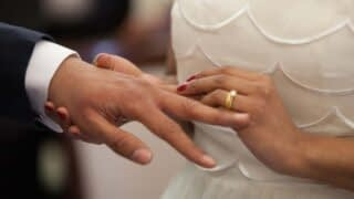 A bride slides a wedding ring on the finger of her husband as they are getting married