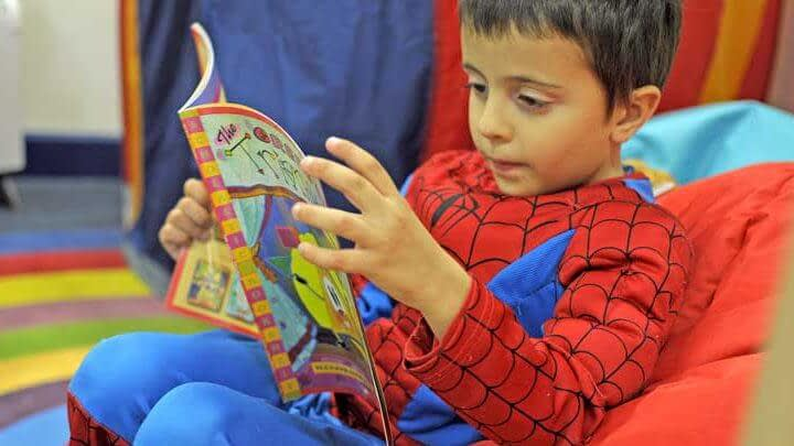 Reception age boy sitting in a red bean bag while reading a picture book