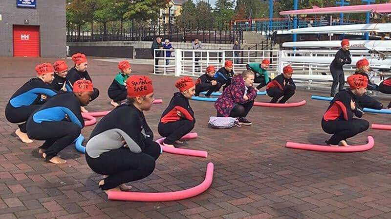 Pupils wearing red bating caps squat during a dry swimming lesson