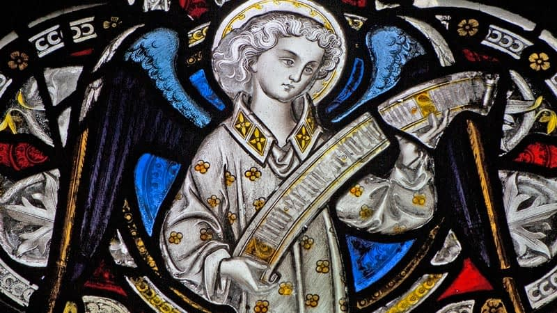 Detail of a stained glass window in Emmanuel depicting an angel holding a scroll