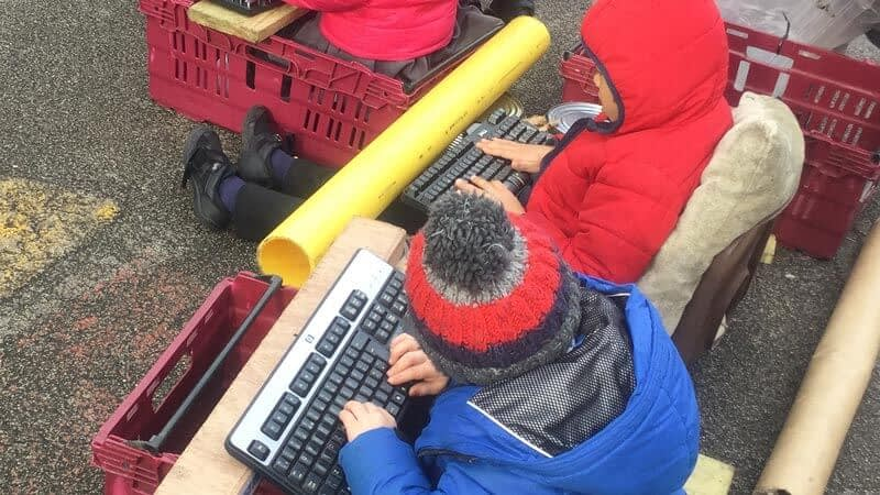 Pupils play with old computer keyboards