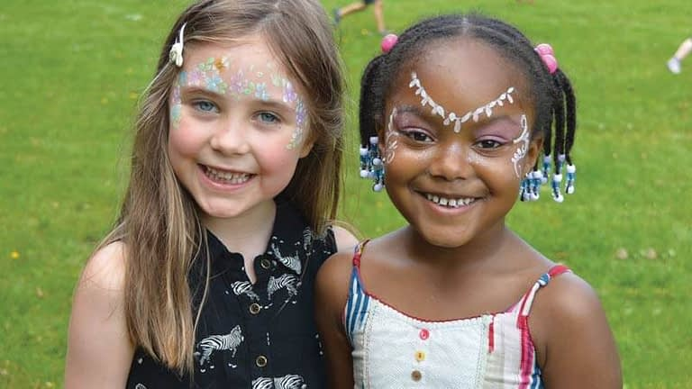 Two smiling pupils from West Didsbury CE, with painted faces at the Great Get Together