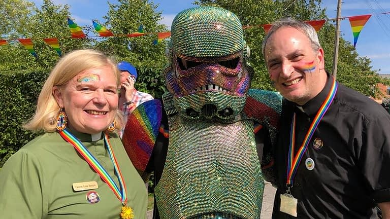 Vicar Lisa and Rector Nick stand either side of a stormtrooper wearing a rainbow shirt