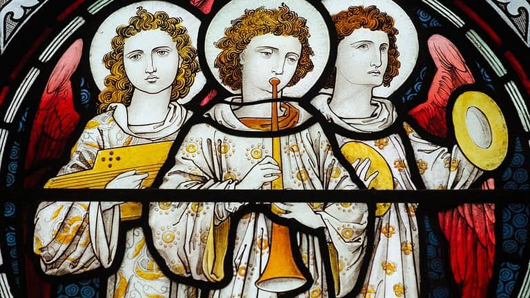 Detail of a stained glass window in Emmanuel depicting three angels, with one playing a trumpet