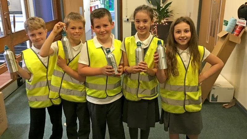 Boys and girls wearing high visibility jackets show off their metal water bottles