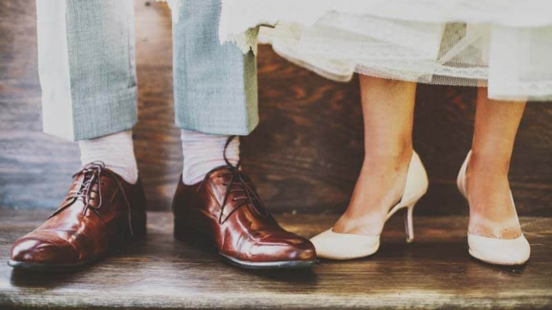 The white high-heeled shows of a bride and the smart brown brogue shows of the groom