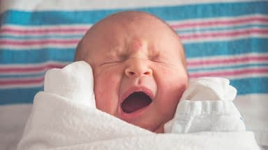 Yawning baby wrapped in white linen