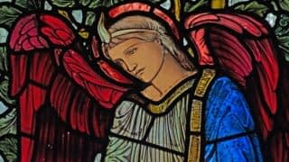 Detail of a stained glass window in Emmanuel depicting an angel in the William Morris window