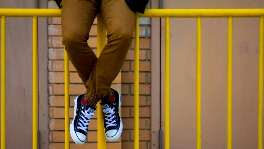 Close up of teenager's dangling legs while sitting on yellow railings