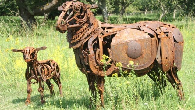 A ewe and her lamb in a field, sculpted in rusted metal parts