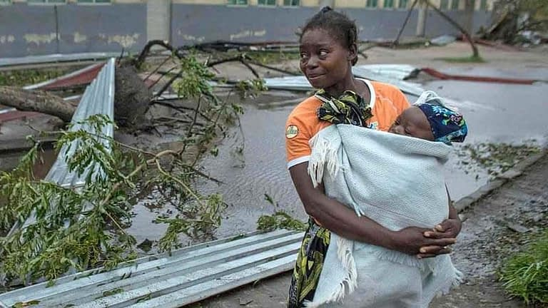 Distressed mother holding her baby amidst home devastated by cyclone