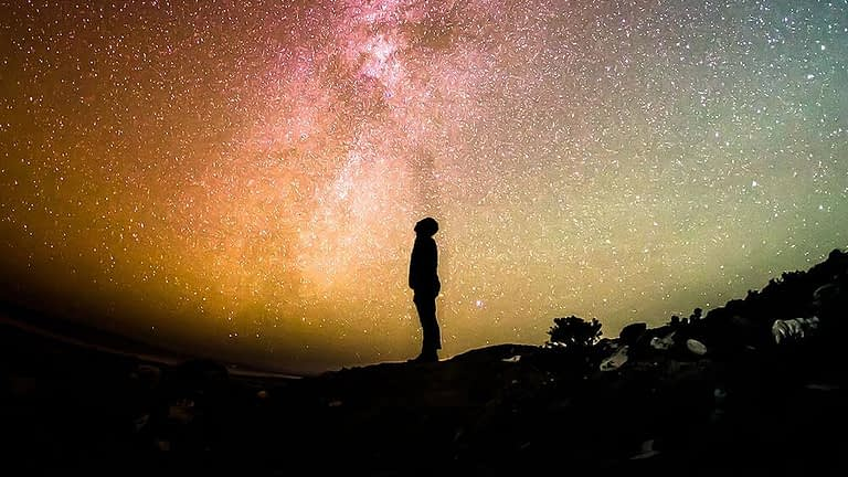 Silhouette gazing up at spectacular stars
