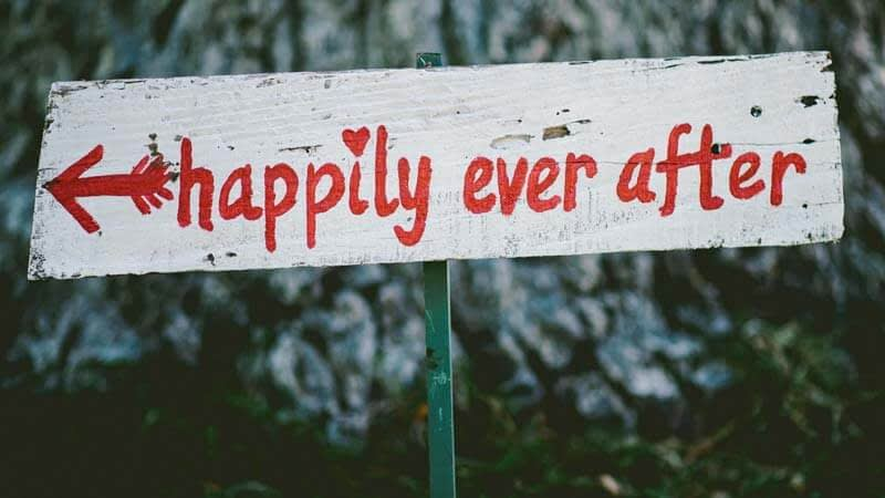 A wooden sign with hand painted text in red: 'happily ever after this way