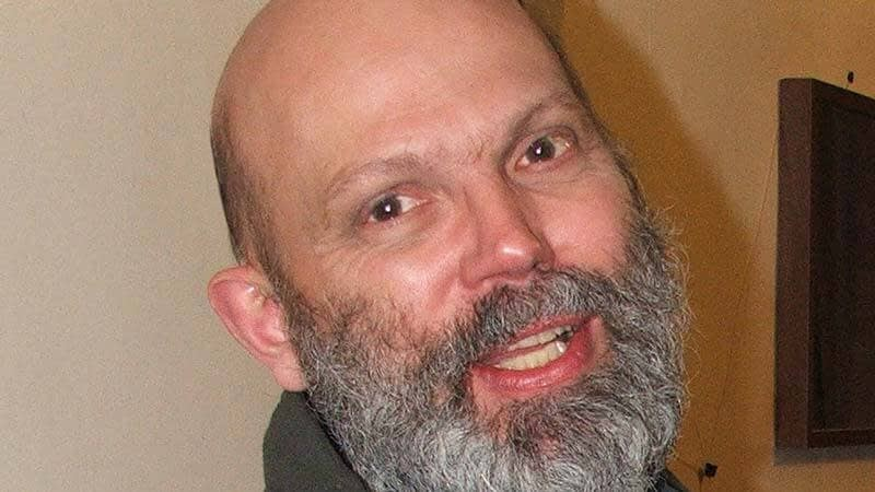 David pictured smiling, with a bushy grey beard