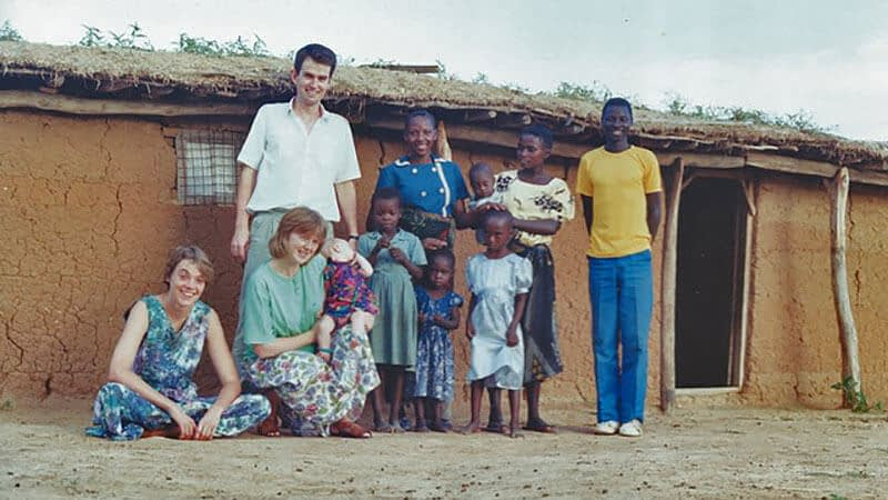 Liz, David and baby Grace with Tanzanian friends in front of a red mud home