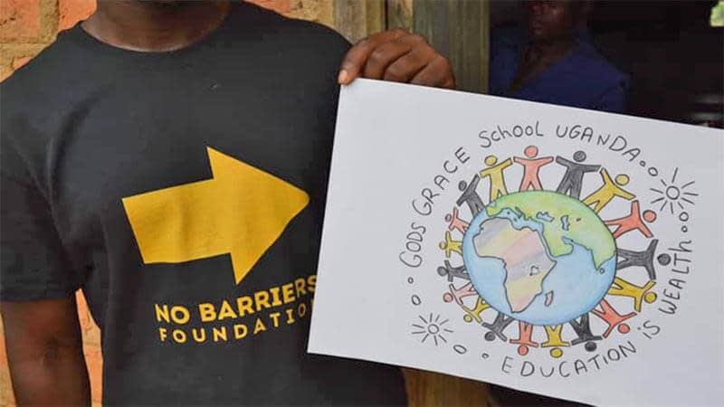 A charity helper holding a poster for God's Grace School