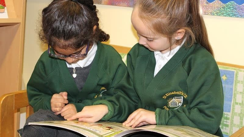 Two girls enjoy reading a book together