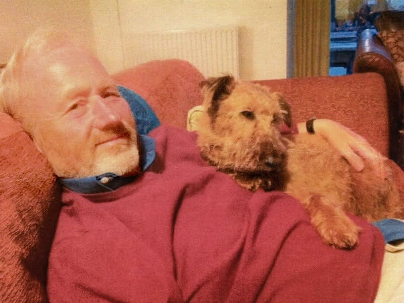 John relaxes on the sofa with his pet terrier